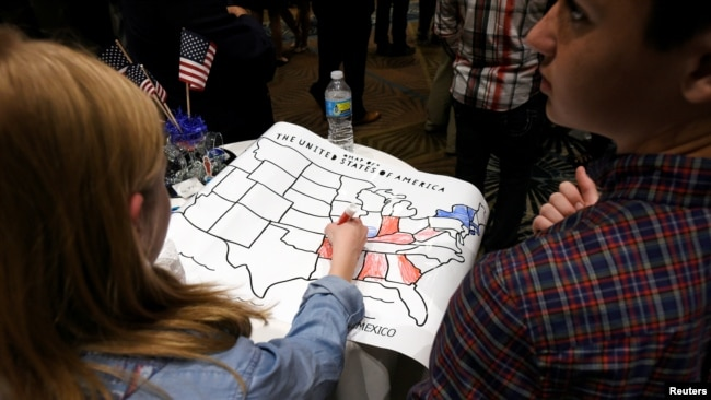 U.S. -- A girls colors an electoral map of the United States in either red or blue as returns are announced for the U.S. general election at election-night party, November 8, 2016.