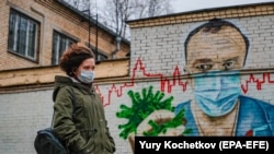 RUSSIA – A woman walks past a mural painting showing a doctor crushing the SARS-CoV-2 coronavirus in his hand, in Moscow, on November 19, 2020.
