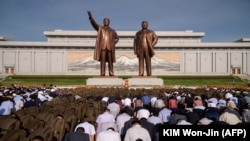 NORTH KOREA - People at Mansu Hill in Pyongyang bow before the statues of the late North Korean leaders Kim Il Sung and Kim Jong Il as the country marks the 25th death anniversary of Kim Il Sung, July 8, 2019
