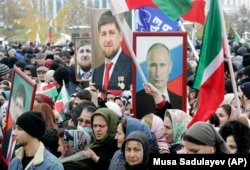 CHECHNYA -- People hold portraits of Russian President Vladimir Putin and Chechen leader Ramzan Kadyrov during a rally marking National Unity Day in Grozny, November 4, 2019