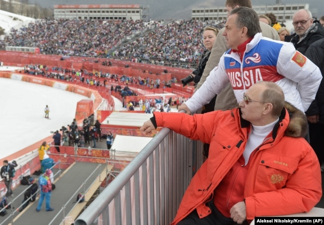 RUSSIA -- Russian President Vladimir Putin, foreground, watches downhill ski competition of the 2014 Winter Paralympics in Roza Khutor mountain district of Sochi, March 8, 2014