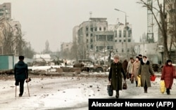 Pedestrians cross a one-legged man in February 1996 in the devastated streets of Grozny.