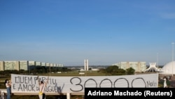 """Artists hold a banner reading """"Who's gone is someone's love, 30,000 dead"""" amid the coronavirus disease (COVID-19) outbreak in Brasilia"""