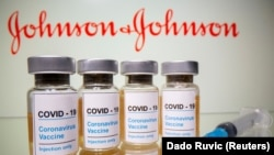 "FILE PHOTO: Vials with a sticker reading, ""COVID-19 / Coronavirus vaccine / Injection only"" and a medical syringe are seen in front of a displayed Johnson & Johnson logo in this illustration taken October 31, 2020."