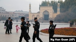 CHINA -- Uighur security personnel patrol near the Id Kah Mosque in Kashgar in western China's Xinjiang region, November 4, 2017.