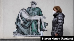 BULGARIA- A woman wearing protective face mask walks past a poster, illustrating a medic in a replica of Michelangelo's Pieta, placed on a wall near vaccination centre at Pirogov hospital, amid the spread of the coronavirus disease (COVID-19), in Sofia, Bulgaria, March 12, 2021.