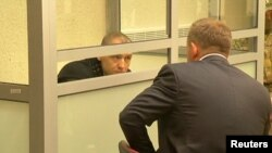 Russia -- A still image from a video footage shows Estonian police officer Eston Kohver talking to a lawyer (R) from a defendants' cage during a court hearing in Pskov, Russia, June 2, 2015.
