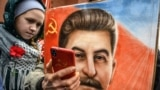 RUSSIA -- A woman, next to a girl, holds a portrait of Soviet leader Josef Stalin and takes a selfie at his grave outside the Kremlin on the Red Square in Moscow, March 5, 2019
