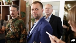 UKRAINE – Alexander Borodai, center, Prime Minister of the self proclaimed 'Donetsk people's republic', listens for a question during his and Igor Strelkov, a pro-Russian separatist commander, left, news conference in Donetsk, July 12, 2014