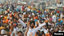 Farmers in the northern state of Punjab gesture as they block a national highway during a protest against farm reform bills passed by India's parliament, September 25, 2020. (REUTERS/Adnan Abidi)