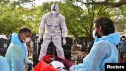 Akshay Mandlik, 37, a professor and a volunteer, wearing personal protective equipment (PPE) prepares to bury the body of a person, who died from the coronavirus disease (COVID-19), at a cemetery in Bengaluru, India, May 18, 2021. REUTERS/Samuel Rajkuma