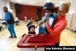 Latvia - A child casts its mother's vote during a general election in Ikskile