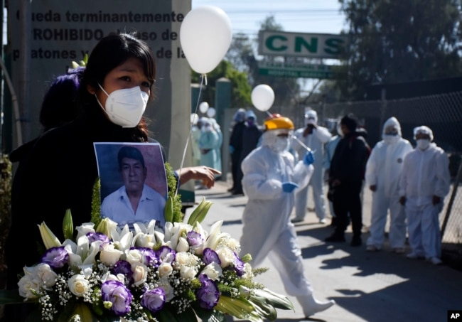 A woman holds a photo of late nurse Marcelino Lopez, who she said died of COVID-10 outside the CNS medical center where he worked in Cochabamba, Bolivia, Thursday, Aug. 6, 2020.