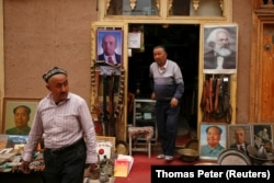 Portraits of China's late Chairman Mao Zedong, Soviet state founder Vladimir Lenin, and German philosopher Karl Marx are displayed outside an antique shop in the old town in Kashgar, Xinjiang Uighur Autonomous Region, China, on March 22, 2017.
