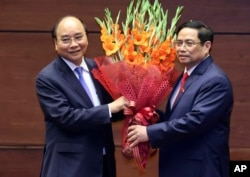 Vietnam's newly elected President Nguyen Xuan Phuc, left, and newly elected Prime Minister Pham Minh Chinh pose for a photo in the National Assembly in Hanoi on April 5.
