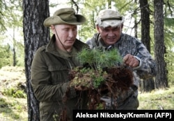 RUSSIA -- Russian President Vladimir Putin and Russian Defense Minister Sergei Shoigu look at vegetation during a short vacation in the remote Tuva region in southern Siberia, August 26, 2018