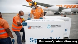 Workers take care of a shipment of Russia's Sputnik V vaccine at the airport in Caracas, Venezuela, on March 29, 2021.