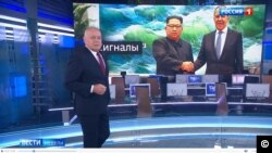 Kiselev in his Sunday show standing in front of an image with Kim Jong Un and Lavrov