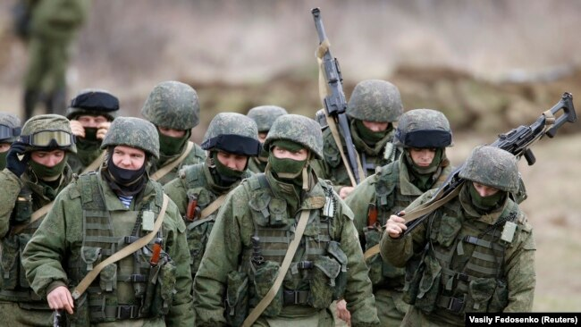 Ukraine - Uniformed men, believed to be Russian servicemen, march outside a Ukrainian military base in the village of Perevalnoye outside Simferopol, March 5, 2014