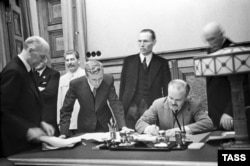 Soviet Union -- USSR. Moscow. Minister of foreign affaires of the USSR Vyacheslav Molotov signs a secret supplement to the Non-aggression Pact between Germany and the USSR (the Molotov-Ribbentrop Pact). Josef Stalin is pictured at the signing ceremony, Moscow, September 28, 1939