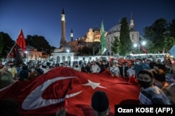 TURKEY -- People, some wearing face masks, wave a giant Turkey national flag and shout slogans outside the Hagia Sophia museum in Istanbul on July 10, 2020.