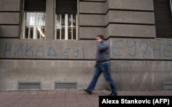 "A pedestrian walks past a ""Never EU!"" graffiti in central Belgrade, December 9, 2011"