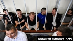 RUSSIA -- Ukrainian sailors sit inside a defendants' cage prior during a hearing at a court in Moscow, July 17, 2019
