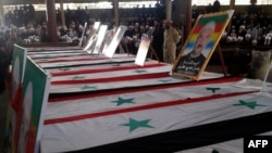 SYRIA - A handout picture released by the official Syrian Arab News Agency (SANA) shows coffins lined up during a mass funeral of yesterday's suicide attacks victims in the southern city of Suwayda on July 26, 2018.