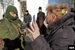 Ukraine -- A Ukrainian woman speaks with an armed man in military uniform, believed to be a Russian soldier blocking the Ukrainian navy base in Novoozerniy village near of Feodosia, Crimea, March 3, 2014