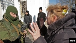 Crimea-- A Ukrainian woman speaks with an armed man in military uniform, believed to be Russian soldiers, block the Ukrainian navy base in Novoozerniy village, March 3, 2014