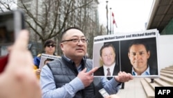 Louis Huang of Vancouver Freedom and Democracy for China holding photos of Canadians Michael Spavor and Michael Kovrig, who have been detained in China since 2018.