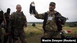 Ukraine -- A pro-Russian separatist holds a stuffed toy found at the crash site of Malaysia Airlines flight MH17, near the settlement of Hrabovo in the Donetsk region, July 18, 2014