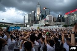 "Protesters gesture as they chant ""no extradition"" as they rally against a controversial extradition law proposal in Hong Kong on June 9, 2019."
