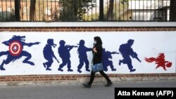 IRAN -- A woman walks past a mural painted on the outer walls of the former U.S. embassy in the Iranian capital Tehran, November 4, 2020.