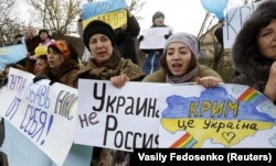 UKRAINE – Participants hold placards and shout slogans during an anti-war rally in the Crimean village of Eskisaray, outside Simferopol, March 10, 2014