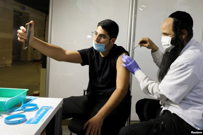 A man receives a vaccination against the coronavirus disease (COVID-19) at a temporary Clalit healthcare maintenance organisation (HMO) vaccination centre, at a sports arena in Jerusalem February 25, 2021. Picture taken February 25, 2021. REUTERS/Ammar Awad