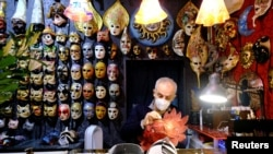 A mask artisan works inside his shop during what would have been Venice's annual colorful carnival, but was canceled this year due to the coronavirus disease (COVID-19) pandemic, in Venice, Italy, February 7, 2021. REUTERS/Manuel Silvestri