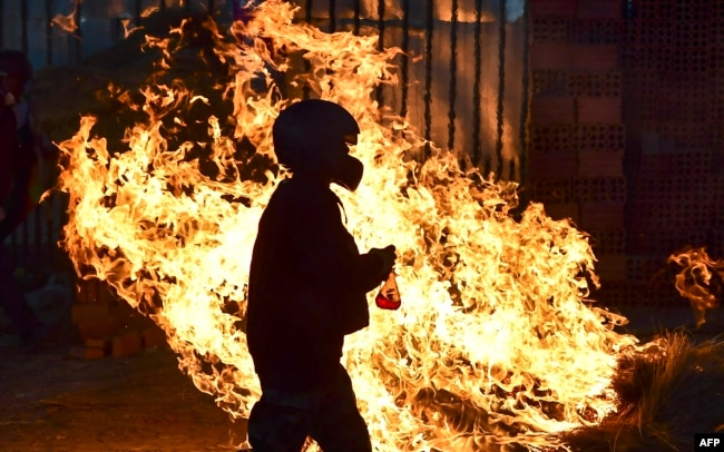 BOLIVIA - A man walks in front a fire blockade set by supporters of Bolivian ex-President Evo Morales in the outskirts of Sacaba, Chapare province, Cochabamba, on November 18, 2019