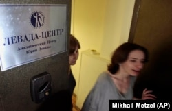 "RUSSIA -- Levada Center employees leave their office with the sign "" Levada-center. Jury Levada analytic center."" in Moscow, May 20, 2013"