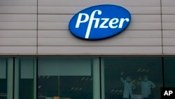 Two workers wave from a window at Pfizer Manufacturing in Puurs, Belgium, on Dec. 2, 2020. (AP Photo/Virginia Mayo)
