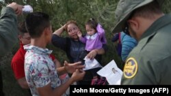 U.S. Border Patrol agents ask a group of Central American asylum seekers to remove hair bands and weddding rings before taking them into custody on June 12, 2018.
