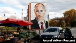 An elderly woman crosses a road in front a mural painting depicting Russian President Vladimir Putin, on the wall of a house, in the town of Kashira, on October 16, 2017.