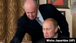 RUSSIA – Evgeny Prigozhin (L) assists Russian Prime Minister Vladimir Putin during a dinner with foreign scholars and journalists at the restaurant Cheval Blanc on the premises of an equestrian complex outside Moscow, November 11, 2011