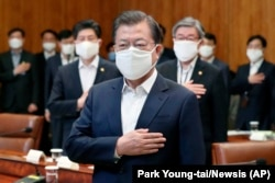 South Korean President Moon Jae-in wearing a mask salutes to a national flag at an emergency meeting on economic response to the coronavirus outbreak at the Presidential Blue House in Seoul, March 30, 2020