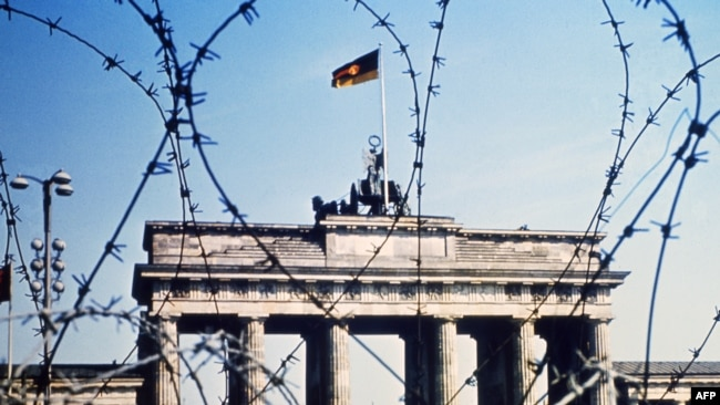 Germany -- FILE -- The Brandenburg Gate is seen through a barbed wire fence, in June 1968. The Berlin Wall was built by the East German government to seal off East Berlin from the part of the city occupied by the three main western powers