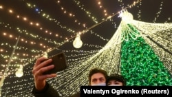 UKRAINE -- A couple wearing protective masks against COVID-19 take a selfie in a front of Christmas tree in central Kyiv, Ukraine December 20, 2020.