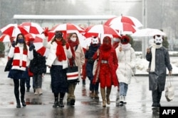 Women wearing carnival masks march carrying umbrellas with the colors of the former white-red-white flag of Belarus to protest against the August 9, 2020, presidential election results in Minsk, Belarus on January 26, 2021.