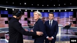 France - French presidential election candidate Marine Le Pen (2ndL) and French presidential election candidate Emmanuel Macron (R) arrive to pose prior to the start of a live brodcast face-to-face televised debate in television studios, Paris, May 03, 2017