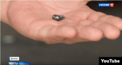 "Shrapnel displayed by an investigator after the bombing. (Screengrab from ""News of the Week with Dmitry Kisleyov, Rossiya 1)."