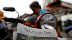 A woman buys the final issue of The Cambodia Daily newspaper at a store along a street in Phnom Penh on September 4, 2017. REUTERS/Samrang Pring